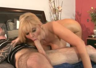 Experienced seductive mature blonde milf Karen Fisher with large juicy ass and massive hanging hooters gives head to younger tattooed stud and rides on his giant hard boner on bed