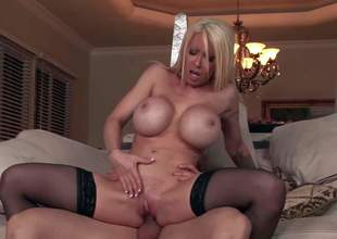 Candy Manson is s blond-haired milf beauty with absolutely amazing huge fake tits. This babe exposes her bombs s she rides stiff cock on the couch in the middle of the room. Watch breasty Candy Manson get shagged