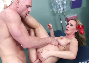 Sexy blonde doctor with giant boobs is attracted to her new patient Johnny Sins. This babe flirts a bit and lets him fuck her hungry pussy on the table.