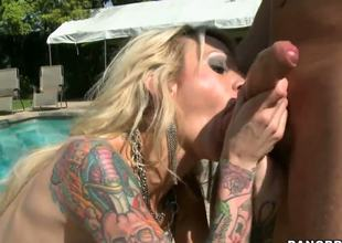 Now thats one crazy, sexy beast with the body of a goddess! Sarah Jessie is a tattooed wild golden-haired who loves big dildos and stiff ramrods and plays with both out by the pool...
