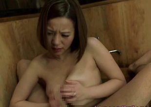 Breasty asian plays with this hard cock