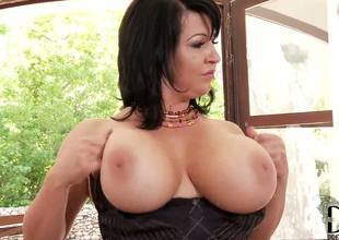 Heavy chested and dark haired milf Kora shows up in sexy dark lingerie and plays with her indeed huge tits in front of the camera guy and makes him indeed horny as she disrobes