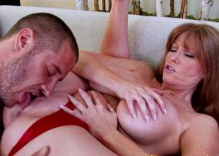Darla Crane is one of those insatiable women that are willing to fuck every young guy. She takes his rock hard dick in her mouth and between her biggest melons previous to it comes to pussy drilling
