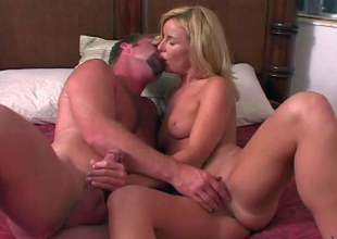 Attractive blonde milf gets her juicy boobies touched by curious man in advance of she takes off her sexy white panties. They warm each other up and then she swallows his rock hard cock
