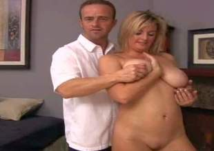 Cheating amateur blonde milf with big natural knockers gets naked while teasing youthful handsome dude in white shirt and takes on his meaty sausage in living room by the fireplace