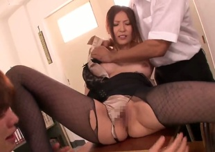This sexual milf from Japan Yuna Shiina looks really breathtaking. She stays in nylons and high heels before getting her wobblers and hairy pussy caressed by two dudes.