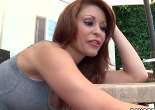 Attractive redhead milf Monique Alexander with consummate hooters and provocative tattoos gives head to slutty muscled stud with meaty pecker in hot outdoor session in point of view