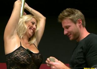 This raunchy blonde milf was showing the guys the location for the charity poker tournament, and she used the excuse to do a little dance routine on the pole. And thats just the start...