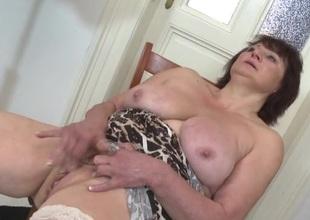 Masturbating granny caresses her big mounds