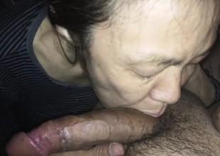 Asian MILF engulfing a white rod